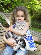 Young girl outdoors smiling with a cat on her lap