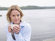 Woman by the water holding a mug