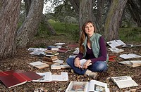 Woman reading book in forest, sitting amongst large group of books cast on ground