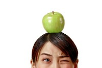 Woman winking her eye while balancing an apple on her head