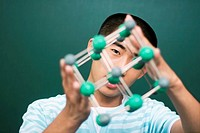 Young man holding molecular structure