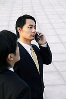 Businessman talking on the phone with his partner standing by his side