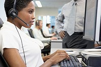 Female office worker wearing headset at computer workstation, supervisor looking on mid section, side view