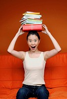 Woman balancing stacked books on her head