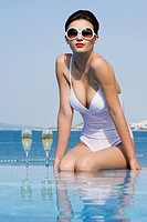 Woman in pool with champagne