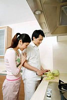 Man cutting vegetables in the kitchen, woman standing by the side