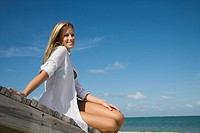 Portrait of young woman sitting on jetty, smiling