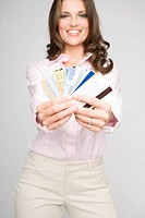 Portrait of young woman holding multiple credit cards focus on foreground