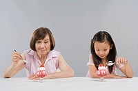 Girl 8-9 and grandmother sitting side by side eating dessert