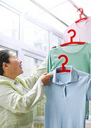 Senior woman hanging clothes in the domestic room
