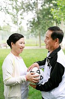 Senior woman passing football to senior man
