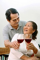 Senior man and woman holding wine glasses