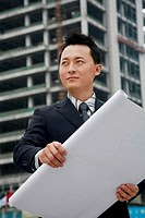 Businessman looking away while holding plan