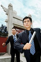 Businessmen running while holding batons