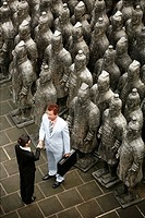 Business people shaking hands beside terracotta soldiers