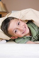Portrait of boy 8-9 under blanket, smiling