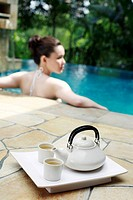 Teapot and teacups on tray, woman resting on edge of swimming pool