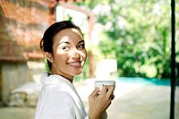 Woman in bathrobe enjoying a cup of coffee