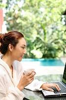 Woman in bathrobe using laptop and having tea