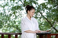 Woman using laptop on the balcony