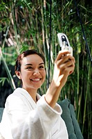 Woman in bathrobe taking picture using her mobile phone