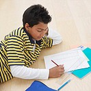 Boy 10-11 doing homework on floor
