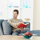 Man holding book sitting on sofa