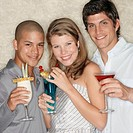 Two young men and woman holding cocktails, smiling, portrait