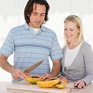 Couple slicing fruit in kitchen