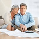 Senior couple calculating finances in living room