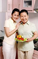 Two women posing with a bowl of vegetables