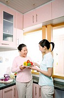 Woman giving a bowl of capsicums to senior woman