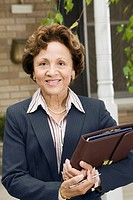Smiling businesswoman with binder of documents