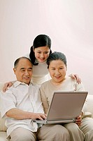 Woman watching senior man and woman using laptop