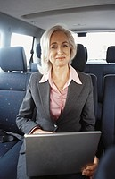 Business woman using laptop in car, portrait