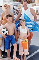 Parents with daughter 8-9 years and son 12-13 years standing with beach toys next to car, elevated view