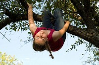 Twelve year old girl hanging upside down from branch of crabapple tree, Winnipeg, Canada