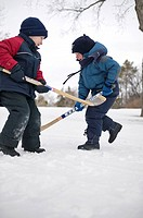 Two young children playing in snow with hockey sticks, Regina, Saskatchewan, Canada