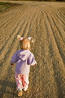 Three year old girl on bare field, Saskatchewan, Canada
