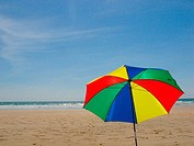Beach scene with colourful umbrella open