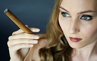 Close_up of young woman smoking cigar