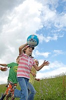 Four children playing with ball in field