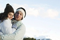 Young couple in winter clothes, embracing, smiling at camera