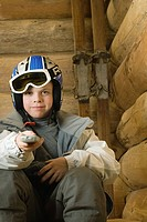 Boy in ski gear pointing remote control at camera