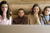 Teen girls and younger boy and girl watching TV together and snacking, front view