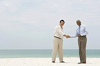 Two businessmen shaking hands on the beach, both smiling at camera