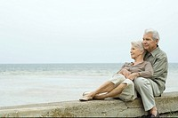 Senior couple sitting together at the beach, embracing, looking at view