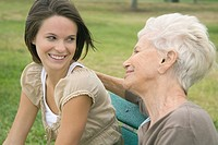 Grandmother and teenage granddaughter sitting together outdoors, smiling at each other