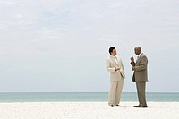 Two businessmen standing face to face at the beach having conversation