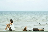 Two young friends looking at ocean, one sitting, the other lying on back